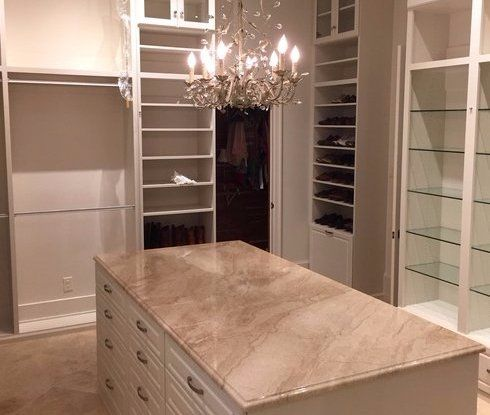 custom closet with island and chandelier