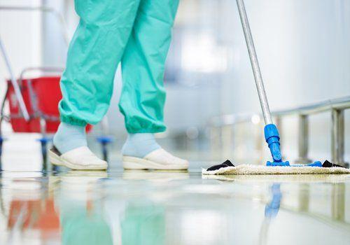 Un impiegato passa il mocio su un pavimento industriale