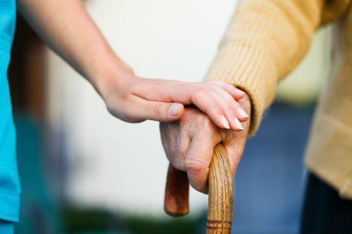 infermiera che mette la propria mano sopra quella di un anziano