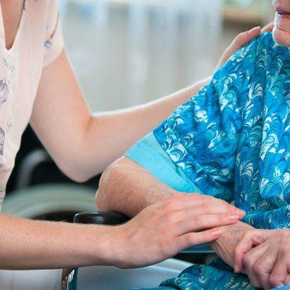 persona che parla con una persona anziana che è seduta su una sedia a rotelle
