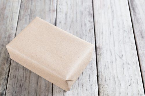 scatola e angolare in cartone su sfondo legno