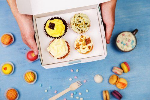 mani che tengono una confezione di quattro muffin aperta e maccarones a contorno su una superficie blu