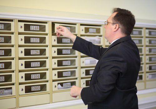 uomo apre la casella di posta nell'atrio del condominio