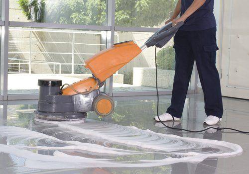 Un operaio passa una monospazzola su un pavimento in marmo