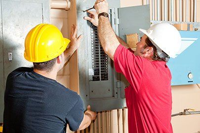 Electricians working together to repair an industrial circuit panel