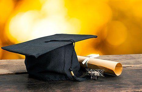 un cappello da laurea,e un foglio arrotolato con un nastro