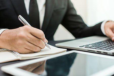 un uomo alla scrivania con una penna in mano e un computer portatile
