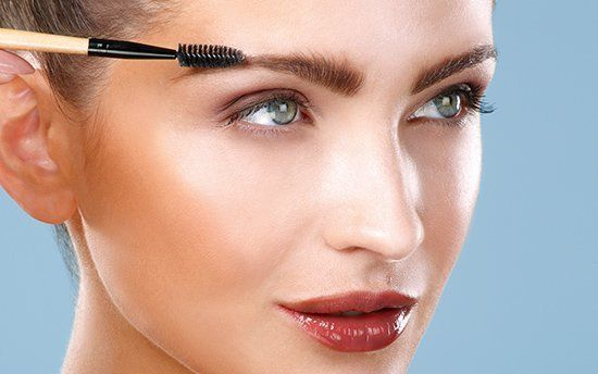 the makeup mirror specialist working on persons eyebrow