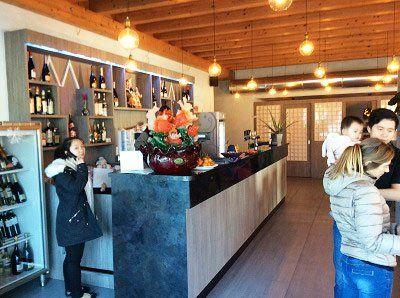 interno del ristorante, sulla sinistra una ragazza dietro al bancone che parla al telefono edi fronte delle persone in piedi