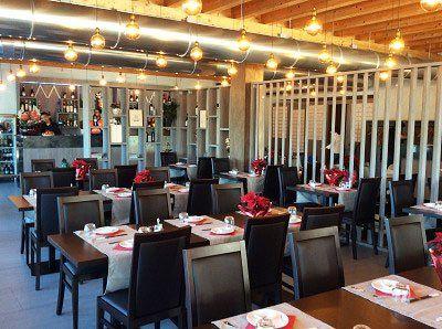 sala da pranzo del ristorante con tavoli e sedie in legno scuro e fiori rossi al centro