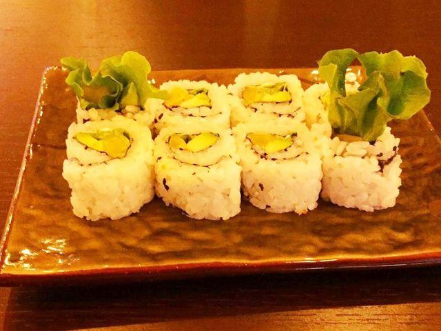 sushi con avocado e fogli di insalata in un piccolo vassoio