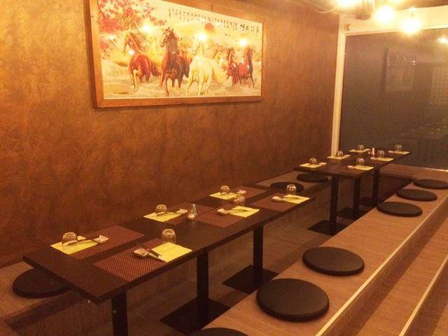 saletta con dei tavoli marroni sulla sinistra e un quadro al muro raffigurante dei cavalli marroni e bianchi