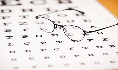 degli occhiali da vista sopra un foglio con delle lettere scritte