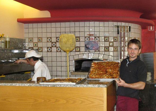 un cameriere che mostra una pizza in una teglia