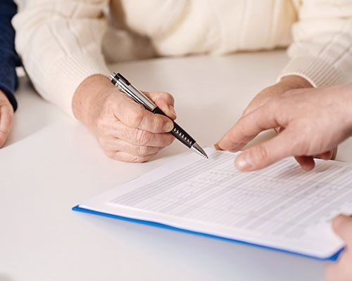un dito che indica un modulo e una mano con una penna che sta per firmarlo
