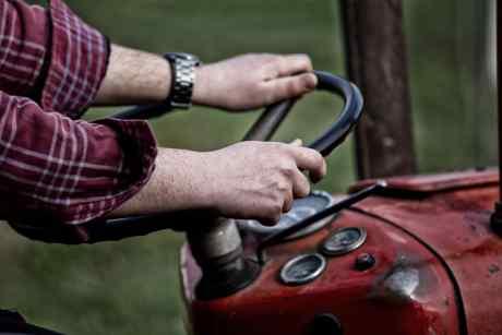 Le mani dell'agricoltore sul volante del trattore