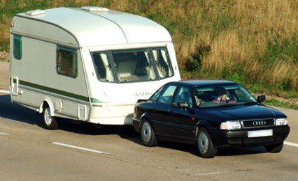 A car pulling a caravan down a road