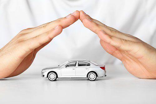 Mani proteggendo un modellino di un'auto