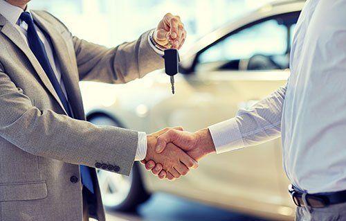 Stretta di mano mentre un uomo dà le chiavi di una macchina a un altro uomo