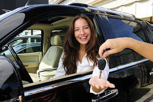 Donna sorridente raccoglie la chiavi dell'automobile