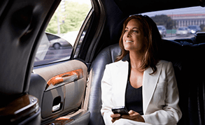 A lady in a white trouser suit, sitting in the back of a taxi