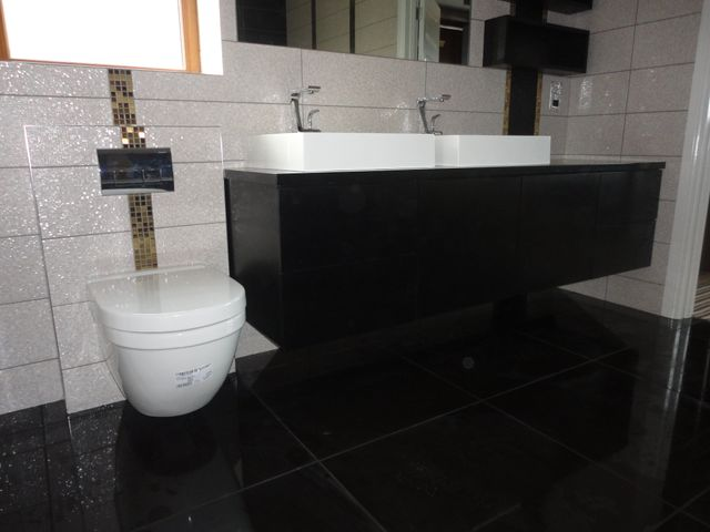 shiny black floor tiles in bathroom