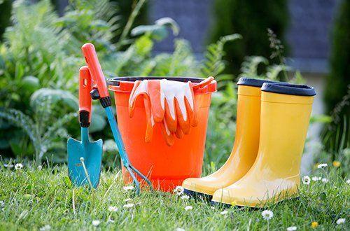 attrezzature da giardinaggio e stivali di gomma gialli su erba