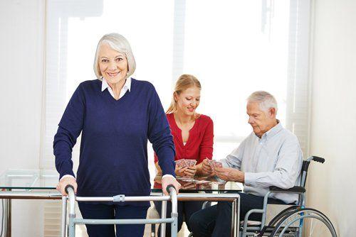 anziana con deambulatore e un`assistente gioca a carte con un anziano sulla sedia a rotelle
