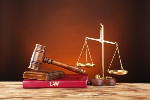 una bilancia a due piatti e un martello di legno sopra a dei libri di giurisprudenza