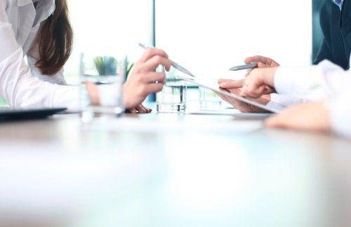una mano di una donna che indica un modulo con la penna e le mani di un uomo che lo tengono