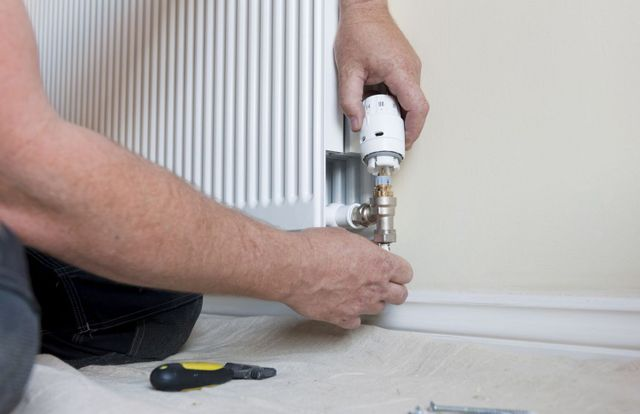 heating and cooling expert repairing a heater in Eagle Bay, NY