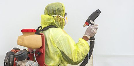 uomo con tuta gialla ,maschera e guanti mentre utilizza un dispositivo per la manutenzione