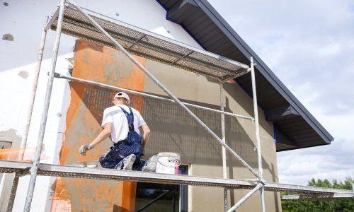 Due operai dipingendo il muro esterno