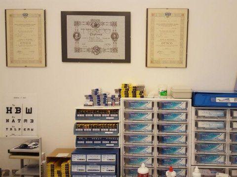 3 quadri con dei diplomi appesi e sotto del mobilio con dei cassetti e altro