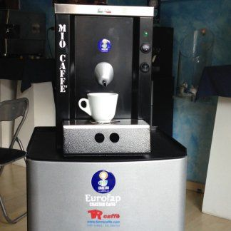 una macchina del caffe grigia e nera con una tazza