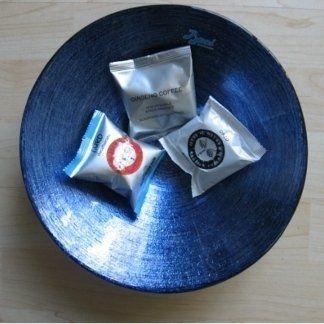 una bacinella blu con dentro tre confezioni di cialde di caffè