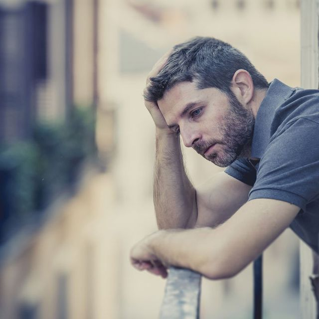 Depressed individual standing in his balcony