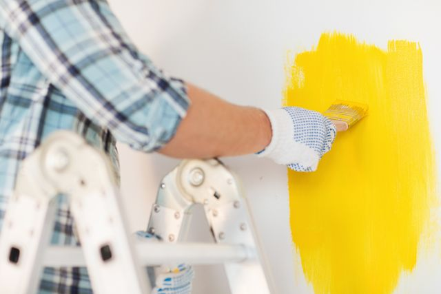 contractor painting interior yellow brush wall ladder