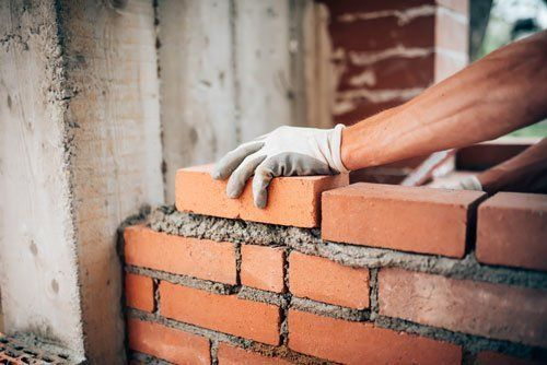 una mano con dei guanti da lavoro bianchi sta posizionando una fila di mattoni su del cemento fresco