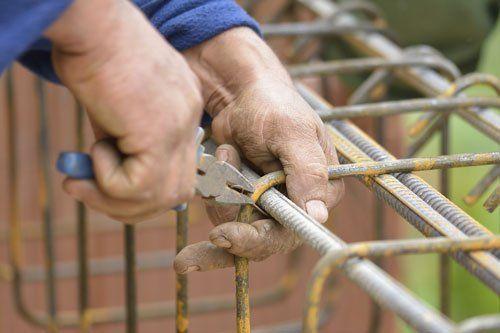 due mani che stringono una piccola sbarra di ferro