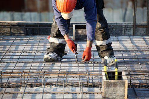 un uomo in tenuta da lavoro nera con elmetto e guanti arancioni é inchinato verso terra e sta stringendo con una pinza una rete metallica