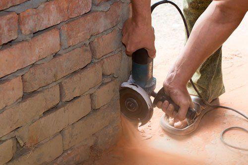 un uomo sta utilizzando un flessibile con disco da taglio sulla parte inferiore di un muro in mattoni