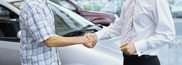 Mechanic and car owner shake hands