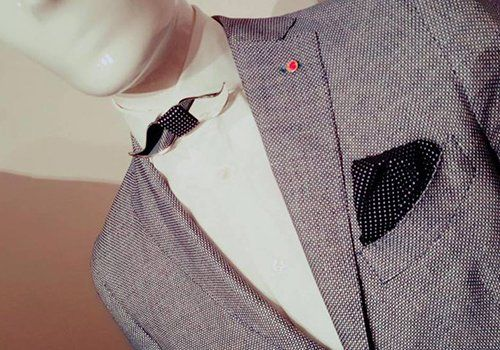 blazer di tweed di tono marrone con fazzoletto nero in l tasca e originale farfallino