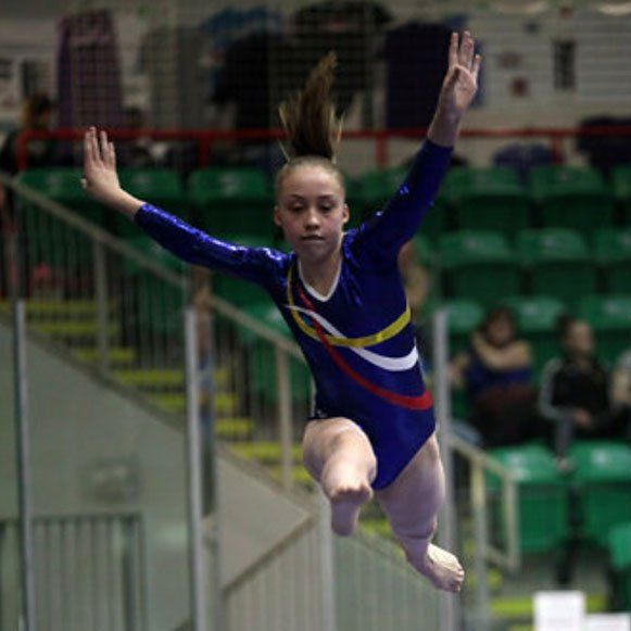 Madi in mid-jump in gymnasium