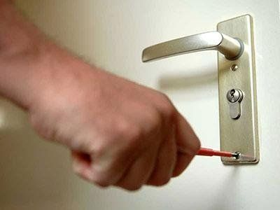 Una mano con un cacciavite che avvita una maniglia di una porta