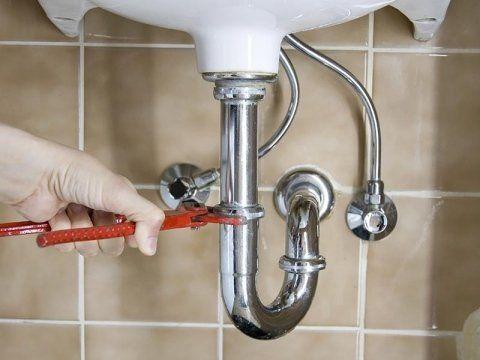 Una mano con un pappagallo che stringe un tubo di un lavabo