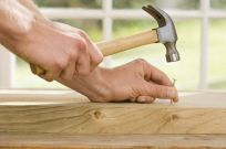 person hammering nail into wood during remodeling services in Wisconsin Rapids, WI