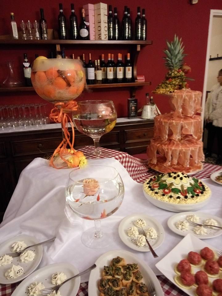 un buffet con dei salumi , tartine e delle bottiglie di vino sulle mensole