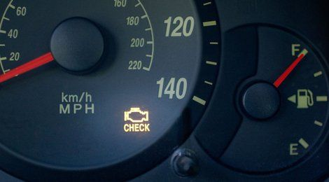 Close up of a car dashboard with the Engine Warning Light Illuminated